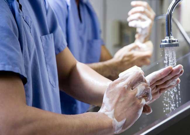الجراح يقوم بتعقيم يديه قبل الجراحة