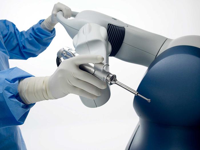 الجراح يحرك يد الروبوت اثناء جراحة المفصل الصناعي
